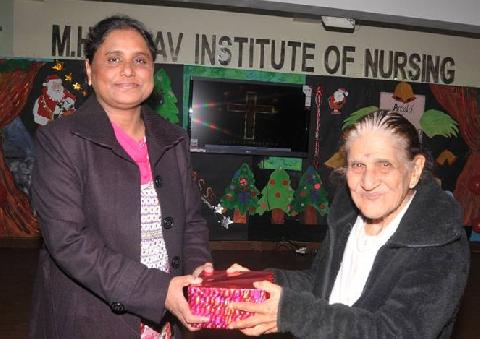 Honorable Chief Guest Mrs. Zeenat Williams giving X-mas Gift to Respected Principal Madam Mrs. Veena Williams